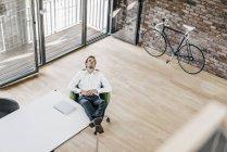 Homme d'affaires assis dans le fauteuil et pensant dans le bureau — Photo de stock