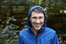 Portrait of smiling man wearing hooded jacket — Stock Photo