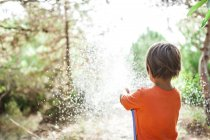 Back view of little boy playing with garden hose — Stock Photo