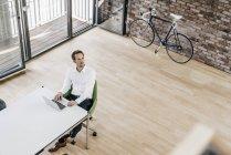 Homme d'affaires utilisant un ordinateur portable dans un bureau moderne — Photo de stock