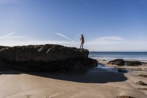 Rear view of teenage girl standing on rock at the beach — Stock Photo