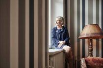 Mulher sênior olhando para fora da janela em casa — Fotografia de Stock