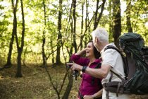 Happy senior couple hiking in a forest — Stock Photo