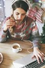 Woman with headphones using laptop while eating Christmas cookie — Stock Photo