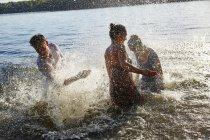 Ludiques amis jouant dans un lac — Photo de stock