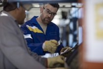 Due riparatori di pneumatici con appunti in fabbrica — Foto stock