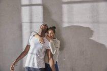 Смеющаяся молодая пара, стоящая перед серой стеной — стоковое фото