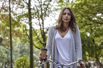 Молодая женщина с кофе пойти и велосипед в парке — стоковое фото