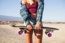 Immagine ritagliata di giovane ragazza bionda in posa con skateboard all'aperto — Foto stock