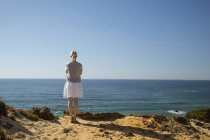 Woman standing at coast, looking at distance — Stock Photo