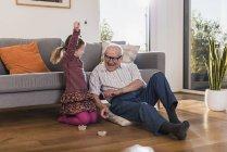 Дедушка и внучка играют на память, девочка празднует победу — стоковое фото