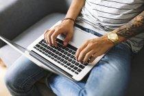 Adolescente sentado en el sofá en casa usando el ordenador portátil, vista parcial - foto de stock