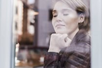 Young woman with closed eyes behind windowpane — Stock Photo