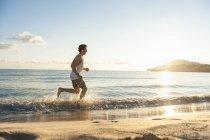 Jeune homme jogging sur la plage en matinée — Photo de stock
