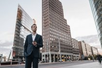 Smiling businessman standing at Potsdamer Platz with smartphone — Stock Photo