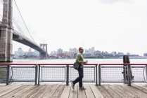 USA, New York City, man walking at East River with coffee to go — Stock Photo