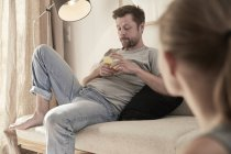 Man at home sitting on couch looking at cell phone with woman in foreground — Stock Photo