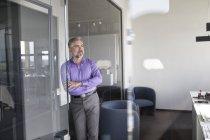 Homme d'affaires debout dans le bureau avec les bras croisés et pensant — Photo de stock