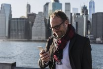 USA, Brooklyn, smiling businessman with earphones using smartphone — Stock Photo