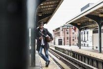 Joven esperando el metro en la plataforma de la estación de tren, usando un teléfono inteligente - foto de stock