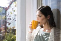 Beautiful caucasian brunette woman drinking coffee at home — Stock Photo