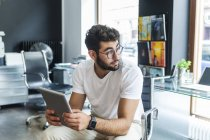 Young man with tablet sitting in a modern office — Stock Photo