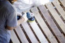 Mann schleift Palette mit einem Zufallsschleifer — Stockfoto
