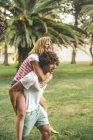 Молодой человек дает девушке прокатиться на свинарнике в парке — стоковое фото