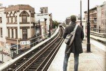 Young man waiting for metro at train station platform — Stock Photo