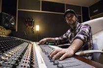 Homem trabalhando na sala de controle de um estúdio de gravação — Fotografia de Stock