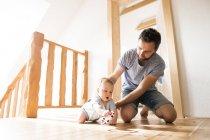 Отец играет с малышом дома — стоковое фото