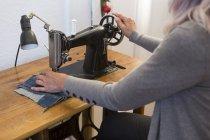 Mulher caucasiana sênior trabalhando na máquina de costura em casa, vista parcial — Fotografia de Stock