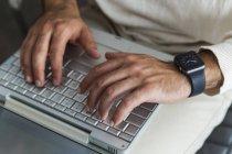 Primer plano de las manos masculinas usando el ordenador portátil - foto de stock
