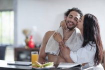 Young woman kissing boyfriend at home during breakfast — Stock Photo
