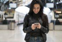 Felice giovane donna con il cellulare in piedi alla stazione ferroviaria — Foto stock