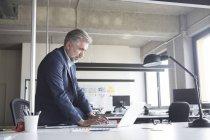 Businessman using laptop in modern office — Stock Photo