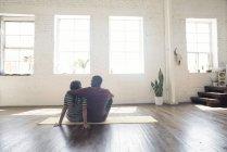 Giovani coppie che si siedono sul tappeto in appartamento loft vuoto — Foto stock