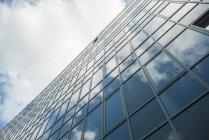 Moderne Glasfassade, die Wolken reflektiert — Stockfoto
