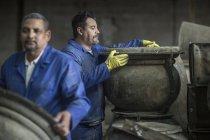 Two men working in industrial pot factory — Stock Photo
