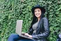 Mujer joven usando laptop al aire libre - foto de stock