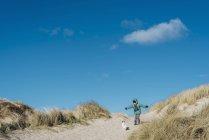 Dänemark, bulbjerg, Junge in warmer Kleidung spielt mit Hund in Dünen — Stockfoto