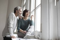 Mature couple looking out of window at home — Stock Photo