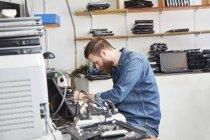Працівник в комп'ютері переробки пластмасових видалення accus з ноутбука — стокове фото