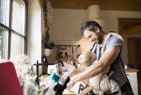 Счастливый отец с ребенком в детской коляске моет посуду — стоковое фото