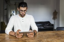 Young man using digital tablet in modern office — Stock Photo