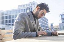 Junger Mann auf der Bank sitzen und mit Mini-tablet — Stockfoto