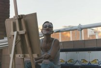 Young woman with easel making funny faces on roof terrace of penthouse — Stock Photo