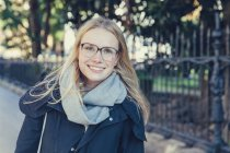 Portrait of smiling young woman with glasses and scarf — Stock Photo