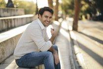 Портрет смеющегося мужчины, сидящего на лестнице и смотрящего в камеру — стоковое фото