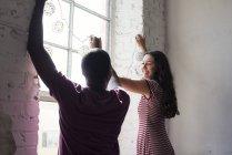 Молодая пара, украшающие окна с fairylights — стоковое фото
